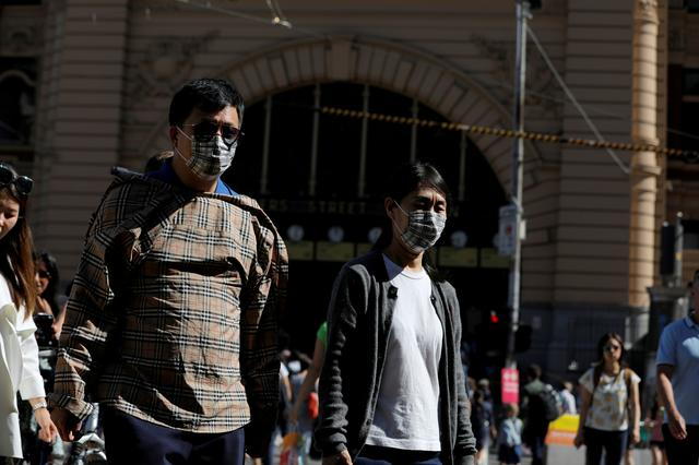 FILE PHOTO: People wearing face masks walk by Flinders Street Station after cases of the coronavirus were confirmed in Melbourne, Victoria, Australia, January 29, 2020. REUTERS/Andrew Kelly