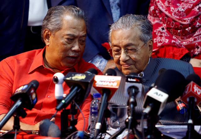 FILE PHOTO: File photo of former Malaysian Prime Minister Mahathir Mohamad listening to current Prime Minister Muhyiddin Yassin during a news conference on April 5, 2018, when both were allies. REUTERS/Lai Seng Sin