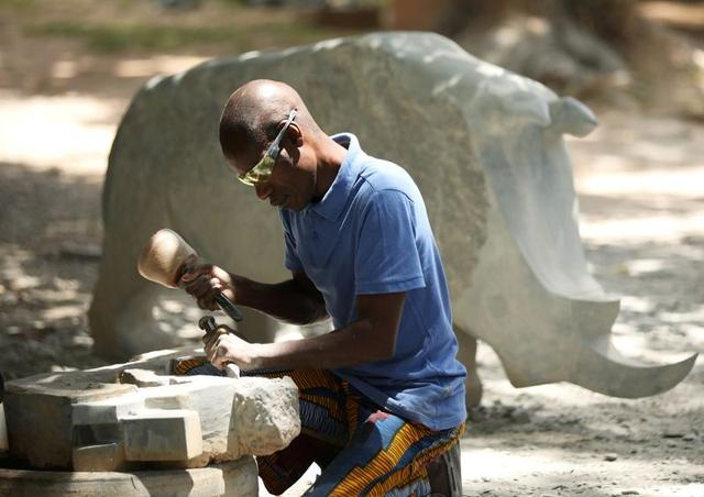 Zimbabwean sculptor Dominic Benhura works on a piece at his studio in Harare, Zimbabwe, March 2, 2020. Picture taken March 2, 2020. REUTERS/Philimon Bulawayo