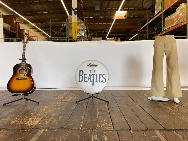 FILE PHOTO: A wooden stage from the Liverpool venue where the Beatles performed before they became famous is displayed in a Julien's Auctions warehouse in Torrence, California, U.S. March 5, 2020, with a pair of pants worn by John Lennon, a guitar played by Paul McCartney and a bass drumhead printed with The Beatles' logo. REUTERS/Jane Ross