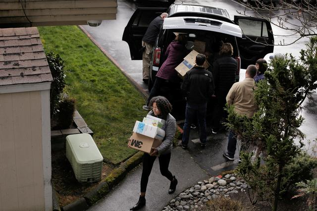FILE PHOTO: People load personal protective equipment and other supplies into a back side entrance of the Life Care Center of Kirkland, the long-term care facility linked to several confirmed coronavirus cases in the state, in Kirkland, Washington, U.S. March 7, 2020.  REUTERS/David Ryder/File Photo