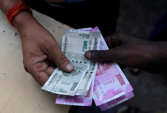 A customer hands Indian currency notes to an attendant at a fuel station in Mumbai, August 13, 2018. REUTERS/Francis Mascarenhas/Files