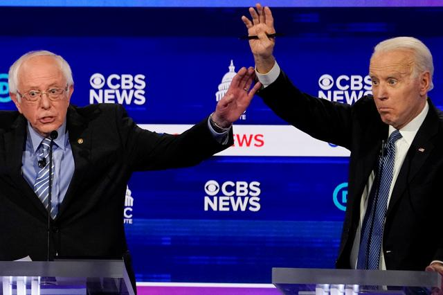 FILE PHOTO: Democratic 2020 U.S. presidential candidates Senator Bernie Sanders and former Vice President Joe Biden brush hands as they have an exchange in the tenth Democratic 2020 presidential debate at the Gaillard Center in Charleston, South Carolina, U.S. February 25, 2020. REUTERS/Jonathan Ernst