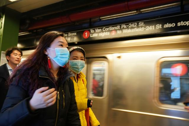 FILE PHOTO: People wear surgical masks in the subway station at Times Square in New York, U.S., January 31, 2020. REUTERS/Bryan R Smith