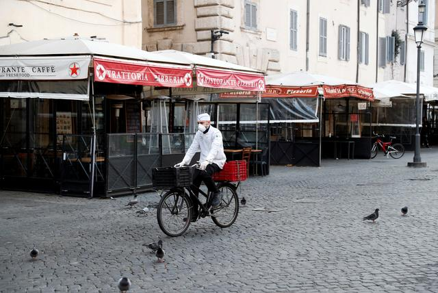 A delivery man wears a protective face mask as he rides a bicycle at Campo de Fiori, after a decree orders for the whole of Italy to be on lockdown in an unprecedented clampdown aimed at beating the coronavirus, in Rome, Italy March 10, 2020. REUTERS/Remo Casilli