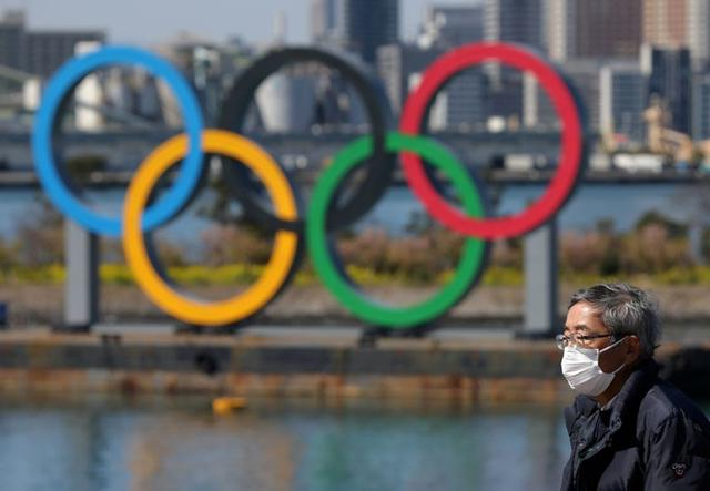 FILE PHOTO: A man wearing a face mask, following an outbreak of the coronavirus, walks in front of giant Olympic rings at the waterfront area at Odaiba Marine Park in Tokyo, Japan, March 6, 2020. REUTERS/Stoyan Nenov