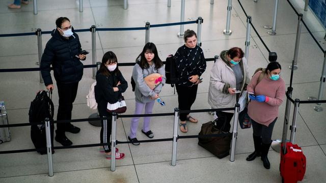 FILE PHOTO: People wait in line to reach TSA immigration process at the John F. Kennedy International Airport in New York, U.S., March 9, 2020. REUTERS/Eduardo Munoz/File Photo