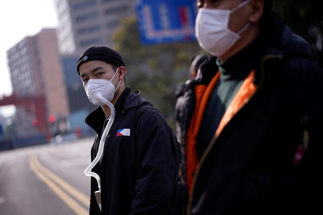 People wearing protective face masks are seen on a crossroads as the country is hit by an outbreak of the novel coronavirus, in Shanghai, China March 10, 2020. REUTERS/Aly Song