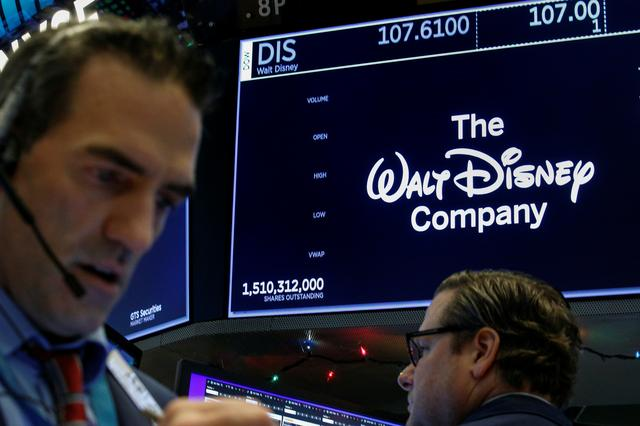 FILE PHOTO: Traders work at the post where Walt Disney Co. stock is traded on the floor of the New York Stock Exchange (NYSE) in New York, U.S., December 14, 2017. REUTERS/Brendan McDermid
