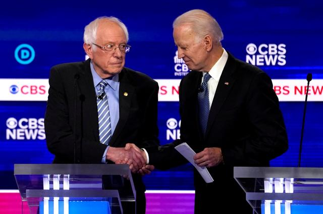 FILE PHOTO: FILE PHOTO: Democratic 2020 U.S. presidential candidates Senator Bernie Sanders shakes hands with former Vice President Joe Biden after the tenth Democratic 2020 presidential debate at the Gaillard Center in Charleston, South Carolina, U.S. February 25, 2020. REUTERS/Jonathan Ernst/File Photo