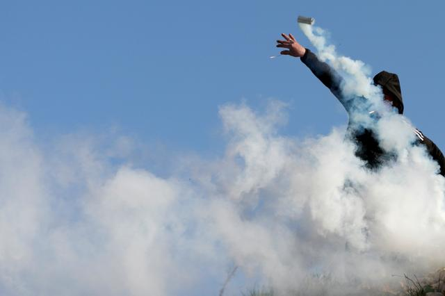 A Palestinian demonstrator hurls a tear gas canister fired by Israeli forces during a protest against Israeli settlements, near the town of Beita in the Israeli-occupied West Bank March 11, 2020. REUTERS/Mohamad Torokman