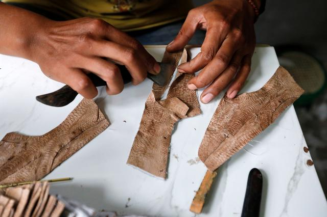 A worker prepares a pattern for a Hirka shoe, made from the skin of chicken feet, at the company's workshop in Bandung, West Java province, Indonesia, February 28, 2020. Picture taken February 28, 2020. REUTERS/Willy Kurniawan