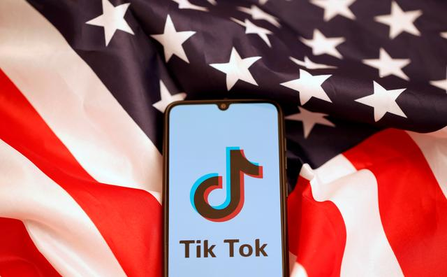 FILE PHOTO: Tik Tok logo is displayed on the smartphone while standing on the U.S. flag in this illustration picture taken, November 8, 2019. REUTERS/Dado Ruvic/File Photo