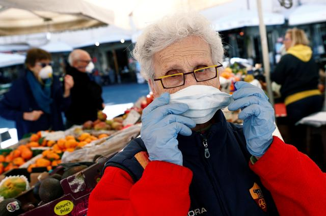 Owner of a fruit stall at Campo de' Fiori market adjusts a protective face mask on the second day of an unprecedented lockdown across all of the country, imposed to slow the outbreak of coronavirus, in Rome, Italy March 11, 2020. REUTERS/Guglielmo Mangiapane