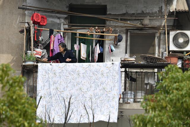 A woman places food out on a balcony to dry at a residential compound in Wuhan, the epicentre of the novel coronavirus disease (COVID-19) outbreak, Hubei province, China, March 10, 2020. REUTERS