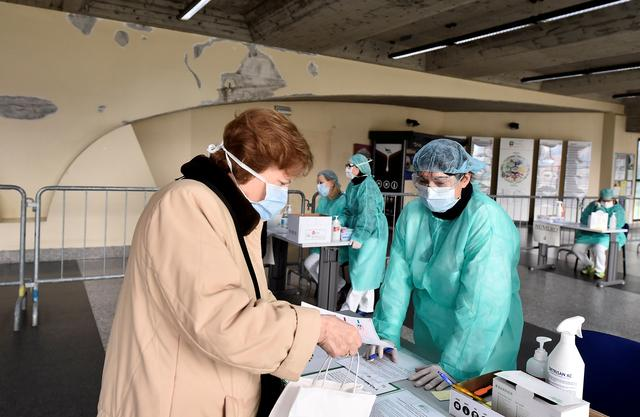 FILE PHOTO: Medical workers wearing protective masks check patients at a medical checkpoint at the entrance of the Spedali Civili hospital in Brescia, Italy March 3, 2020.  REUTERS/Flavio Lo Scalzo