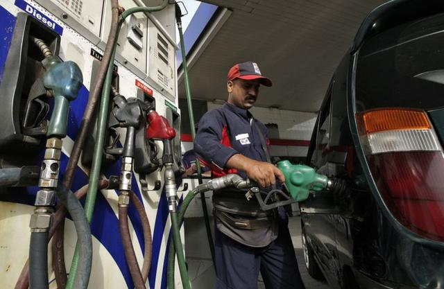 An employee fills a vehicle with petrol at a fuel station in New Delhi June 25, 2010. India's government on Friday freed up state-subsidised petrol prices and hiked other fuels as high global oil prices and pressure to trim the budget deficit outweighed concerns about the political impact of the measures. REUTERS/Mukesh Gupta (INDIA - Tags: ENERGY BUSINESS POLITICS)