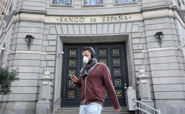 FILE PHOTO: A man wears a protective face mask as he walks past Banco de Espana (Bank of Spain), amidst concerns over coronavirus outbreak, in Barcelona, Spain March 14, 2020. REUTERS/Nacho Doce/File Photo
