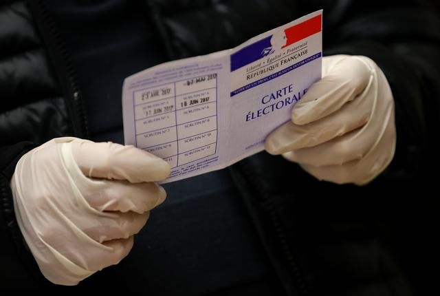 An official wearing latex gloves holds an electoral card at a polling station during the first round of mayoral elections in Strasbourg as France grapples with an outbreak of coronavirus disease (COVID-19), in Strasbourg, France March 15, 2020. REUTERS/Christian Hartmann
