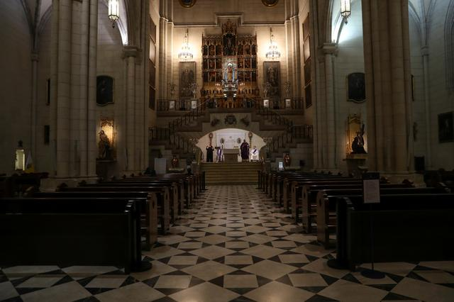 Three people attend a mass at La Almudena Cathedral that is being lived streamed after Catholic masses were suspended during a partial lockdown as part of a 15-day state of emergency to combat the coronavirus disease outbreak, in Madrid, Spain March 15, 2020. REUTERS/Susana Vera