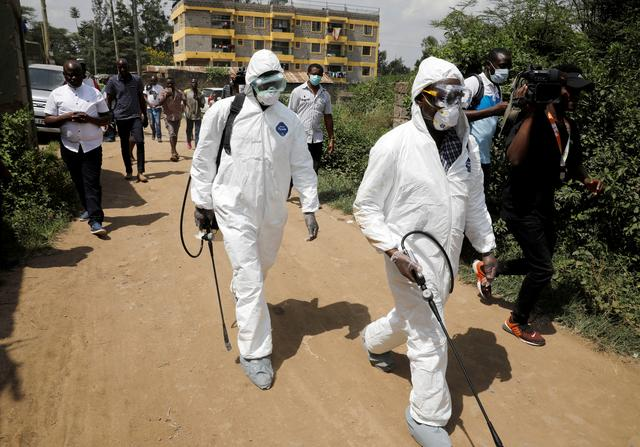 FILE PHOTO: Kenyan health workers dressed in protective suits walk after disinfecting the residence where Kenya's first confirmed coronavirus patient was staying, in the town of Rongai near Nairobi, Kenya March 14, 2020. REUTERS/Baz Ratner/File Photo