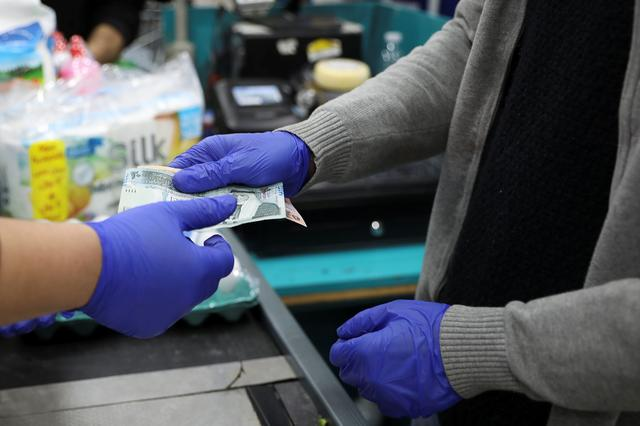 A cashier wearing gloves amid concerns over the coronavirus (COVID-19) spread works at a mall in Amman, Jordan, March 15, 2020.REUTERS/Muhammad Hamed