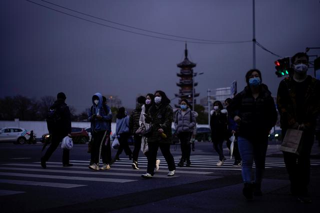 FILE PHOTO: People wearing protective face masks are seen on a crossroads as the country is hit by an outbreak of the novel coronavirus, in Shanghai, China March 9, 2020. REUTERS/Aly Song