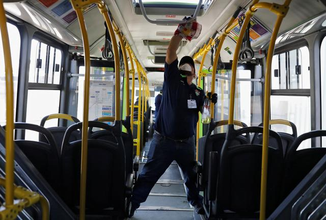 FILE PHOTO: A worker wears a protective face mask works while cleaning the interior of a public bus, amid concerns over the spread of coronavirus disease (COVID-19), in Guatemala City, Guatemala March 15, 2020. REUTERS/Luis Echeverria