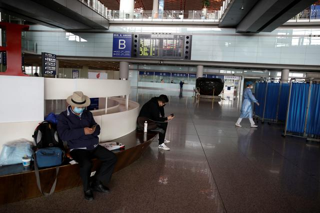 People wearing face masks look at their cellphones at Beijing Capital International Airport, as the country is hit by an outbreak of the novel coronavirus, in Beijing, China March 16, 2020. REUTERS/Carlos Garcia Rawlins