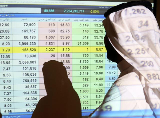 FILE PHOTO: A Saudi man stands in front of a screen of stock prices at ANB Bank in Riyadh, Saudi Arabia March 15, 2020. REUTERS/Ahmed Yosri/File Photo