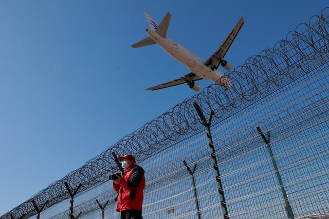 FILE PHOTO: A man wearing a protective mask stands at a fence surrounding Beijing Capital International as a plane lands in Beijing as the country is hit by an outbreak of the novel coronavirus, China, March 13, 2020. REUTERS/Thomas Peter