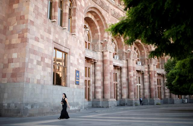 FILE PHOTO: A woman walks in front of the government headquarters at the Republic square in Yerevan, Armenia, May 3, 2018. REUTERS/David Mdzinarishvili