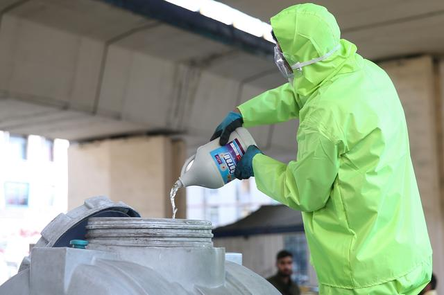 FILE PHOTO: A member of a medical team wears a protective face mask, following the coronavirus outbreak, as he prepares disinfectant liquid to sanitise public places in Tehran, Iran March 05, 2020. WANA (West Asia News Agency)/Nazanin Tabatabaee via REUTERS