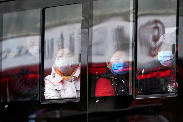 People wear protective face masks on a bus following an outbreak of coronavirus disease (COVID-19), in downtown Shanghai, China March 16, 2020. REUTERS/Aly Song