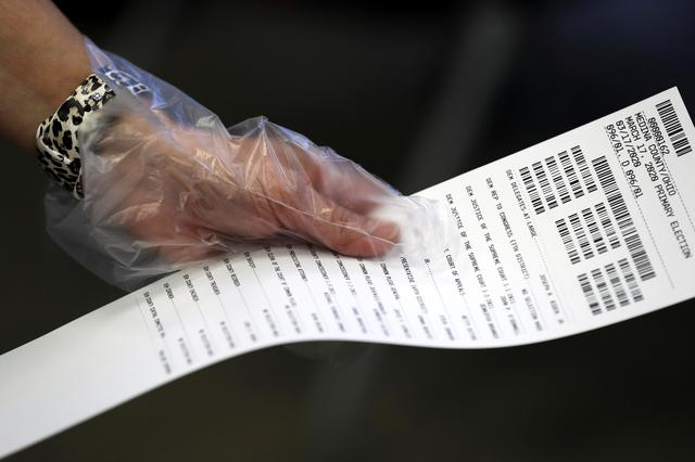 A person wears protective gloves during early voting for the Ohio primary election at the board of elections in Medina, Ohio, U.S. March 16, 2020. REUTERS/Aaron Josefczyk