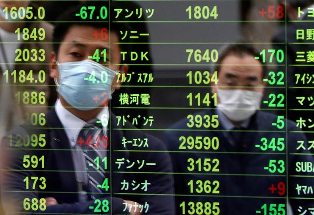 Passersby wearing protective face masks following an outbreak of the coronavirus disease (COVID-19) are reflected on a screen displaying stock prices outside a brokerage in Tokyo, Japan, March 17, 2020. REUTERS/Issei Kato