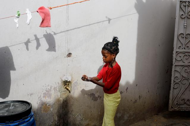 A girl washes her hands at the entrance of her parents' house in Pikine, on the outskirts of Dakar, Senegal March 9, 2020.  REUTERS/Zohra Bensemra