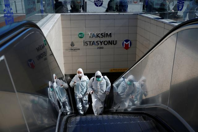 Municipality workers in protective suits disinfect entrance of Taksim metro station, due to coronavirus disease (COVID-19) concerns, in central Istanbul, Turkey, March 17, 2020. REUTERS/Kemal Aslan