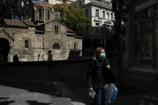 A woman wears a protective face mask as she walks next to a church in Athens, Greece, March 17, 2020. REUTERS/Costas Baltas