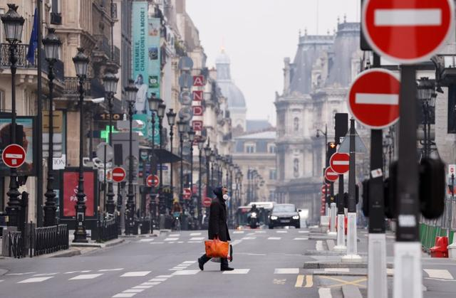 FILE PHOTO: A man wearing a protective face mask crosses the deserted Rue de Rivoli in Paris as a lockdown is imposed to slow the rate of the coronavirus disease (COVID-19) in France, March 18, 2020.  REUTERS/Christian Hartmann