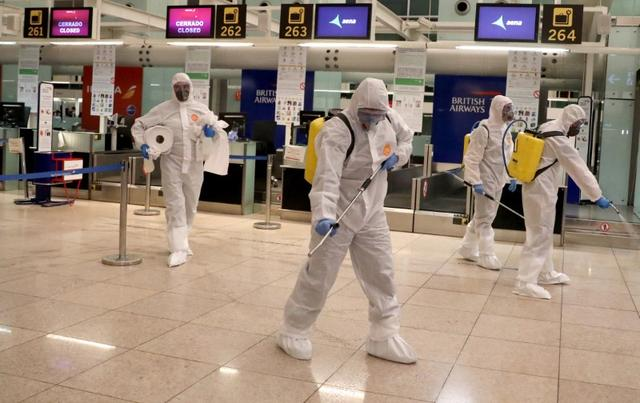 Members of the Military Emergency Unit (UME) disinfect the Josep Tarradellas Barcelona-El Prat Airport during a partial lockdown as part of a 15-day state of emergency to combat the coronavirus disease (COVID-19) outbreak in Barcelona, Spain March 19, 2020. REUTERS/Nacho Doce