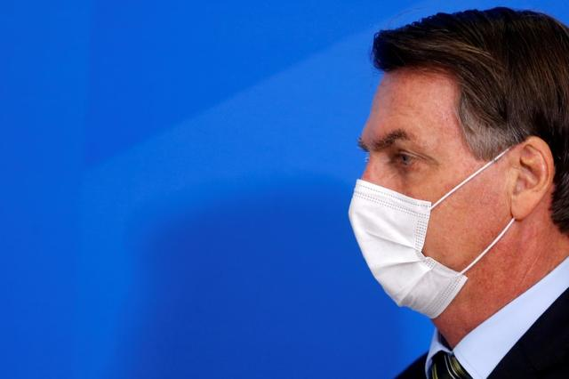 Brazil's President Jair Bolsonaro wearing a protective face mask arrives to a press statement to announce federal judiciary measures to curb the spread of the coronavirus disease (COVID-19) in Brasilia, Brazil March 18, 2020. REUTERS/Adriano Machado