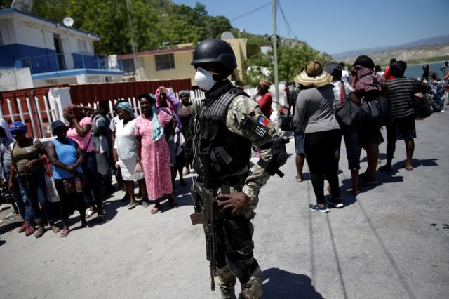 FILE PHOTO: A Haitian National Police (PNH) officer looks on as Haitians stand behind him in the in the border of Malpasse, Haiti, March 17, 2020. Haiti has suspended flights from Europe, Latin America and Canada and impose major restrictions on the border with the neighboring Dominican Republic to prevent the spread of coronavirus disease (COVID-19). REUTERS/Andres Martinez Casares