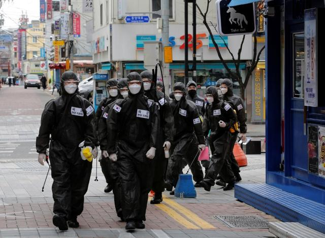 FILE PHOTO: South Korean soldiers in protective gear make their way while they disinfect buildings downtown, following the rise in confirmed cases of coronavirus disease (COVID-19) in Daegu, South Korea, March 15, 2020. REUTERS/Kim Kyung-Hoon