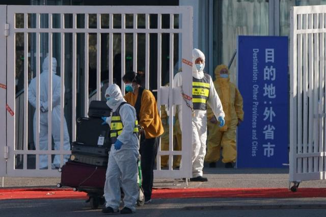 FILE PHOTO: March 17, 2020 picture of staff in protective suits accompanying a passenger outside a centralized facility for screening and registration near the Beijing Capital International Airport in Beijing as the country tries to contain imported cases of the coronavirus. REUTERS/Thomas Peter