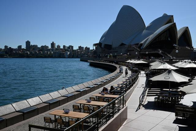 FILE PHOTO: Tables at an open restaurant are seen mostly deserted on a quiet morning at the waterfront of the Sydney Opera House, where scheduled public performances have been cancelled due to the coronavirus disease (COVID-19), in Sydney, Australia, March 18, 2020.  REUTERS/Loren Elliott