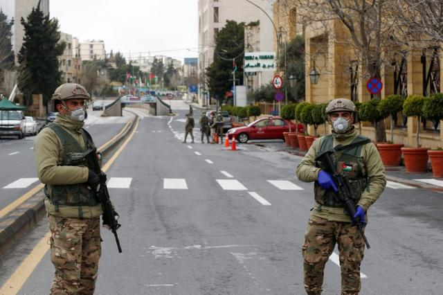 Jordanian army members stand guard at a check point after the start of a nationwide curfew, amid concerns over the coronavirus disease (COVID-19) spread, in Amman, Jordan March 21, 2020. REUTERS/Muhammad Hamed