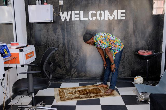 FILE PHOTO: Brown, 33, a barber, performs Friday prayer in his shop as mosques are closed over concerns of the spread of coronavirus disease (COVID-19) in Medina, neighbourhood of Accra, Ghana March 20, 2020. REUTERS/Francis Kokoroko/File Photo