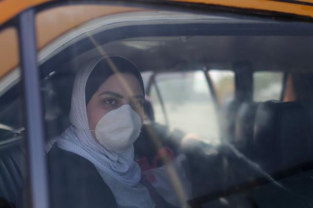 FILE PHOTO: A Palestinian woman, wearing a mask as a preventive measure against coronavirus, looks out of a car upon her return from abroad, at Rafah border crossing in the southern Gaza Strip March 8, 2020. REUTERS/Ibraheem Abu Mustafa/File Photo