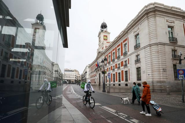 People wearing protective face masks are seen in an almost empty Puerta del Sol during a partial lockdown, which is a part of a 15-day state of emergency to combat the coronavirus disease (COVID-19) outbreak in Madrid, Spain, March 21, 2020. REUTERS/Sergio Perez